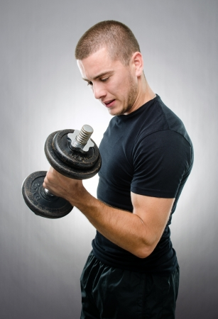 Studio shot of handsome man with a dumbbell on gray background