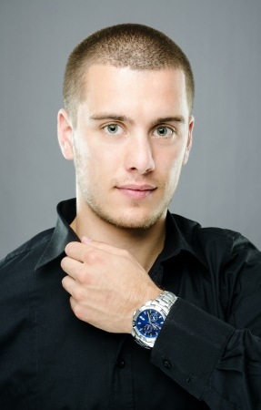 Studio shot of handsome young man with blue luxury watch Stock Photo