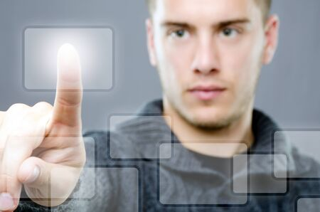 Young man pressing a modern touch button on virtual display photo