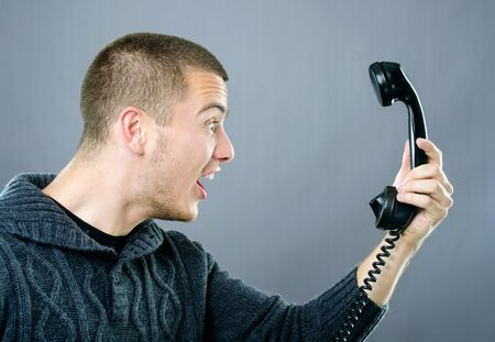 Upset young man with funny facial expression yelling on phone Stock Photo