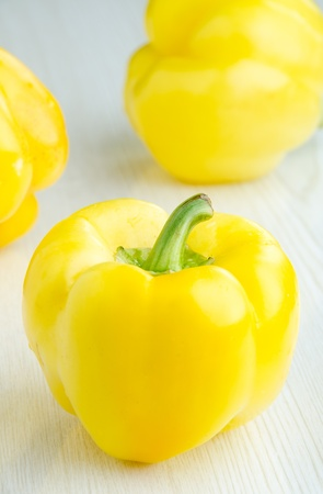 Fresh yellow pepper on white kitchen table - selective focus