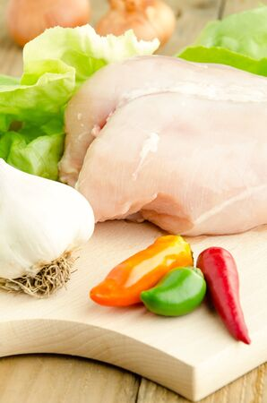 Raw chicken breasts on cutting board with various vegetables and salad