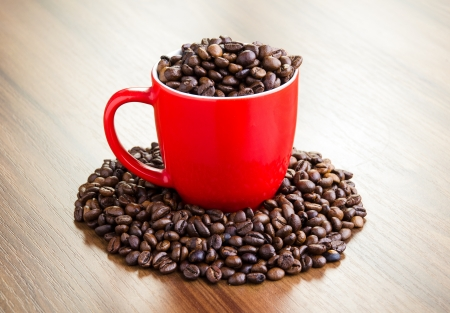 Red cup full of coffee beans on wooden table