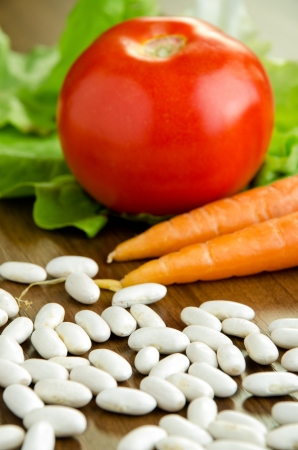 Close up shot of uncooked white beans and fresh vegetables - selective focus Stock Photo
