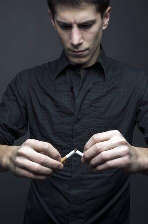 Studio shot of young man with a broken cigar - no smoking concept