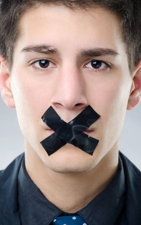 gagged: Portrait of young man with black X tape over his mouth Stock Photo