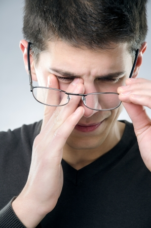 Young man rubs his eyes - eyesight problem concept photo