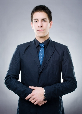Studio shot of serious young man in black suit