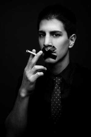 Young man struggling to quit smoking - low key Stock Photo