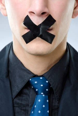 gagged: Close up shot of a man with black tape over his mouth - censored speech concept