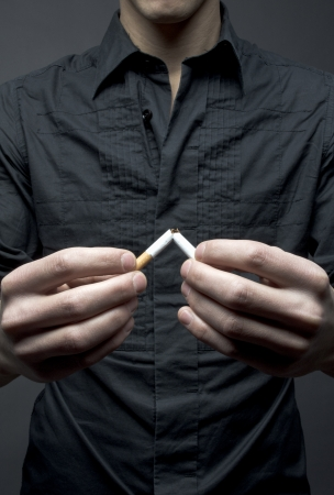 Man breaks cigarette - smoking cessation concept