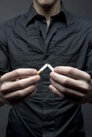 Man breaks cigarette - smoking cessation concept