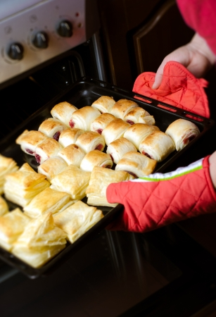 Housewife takes out a freshly baked puff pastry from the oven - shallow DOF