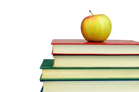 Apple on top of the pile of books isolated on white