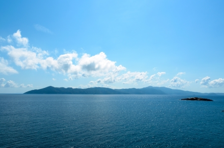 Rocky island in the distance over the beautiful blue sea Stock Photo