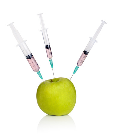 Syringes flung into green apple isolated on white - GMO concept Stock Photo