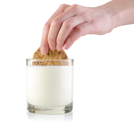 Female hand dunking cookie in milk isolated on white