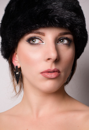 Attractive pensive young woman with bare shoulders in a winter hat looking off to the side with her eyes with a thoughtful expression Stock Photo