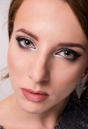 grey eyed: Close up beauty portrait of a lovely young grey eyed woman wearing trendy eye makeup looking into the lens with a serious expression