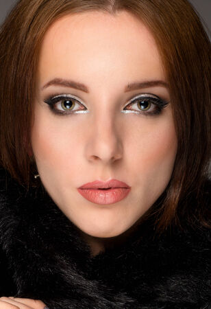 enigmatic: Close up face portrait of a serene young brunette woman wearing elegant makeup in a winter scarf looking directly at the camera with a serious enigmatic expression