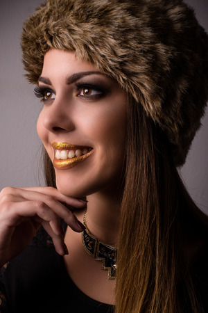 Vivacious smiling winter fashion model in a fur hat and knitwear looking to the side with her hand to her chin, close up face portrait Stock Photo