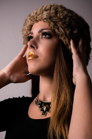 Close up Attractive Young Woman Wearing Furry Hat, Fashionable Necklace and Black Shirt, Looking Up with Both hands Touching the Head. Isolated on Light Brown Background.