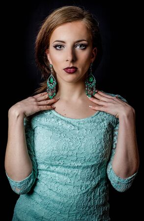 Close up Gorgeous Young Woman Posing in Elegant Mint Green Dress and Earrings with Both Hands on her Shoulders While Looking at the Camera, Isolated on Black Background.