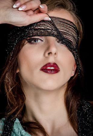 sensually: Close up Gorgeous Young Woman with Makeup, Pulling up the Black Net on her Face While Looking at the Camera Sensually, on a Black Background