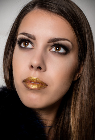 Close up Pretty Long Hair Young Woman with Gold Lips Make up Looking Up on a Gray Background Stock Photo