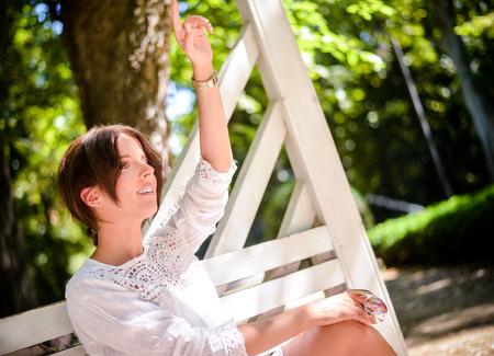 caras felices: Atractiva mujer joven sentada en el banco del parque por la mañana, levantando su brazo mientras llamar a alguien desde lejos