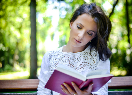 Waist Up Portrait of Brunette Woman Wearing Lace Top Engrossed in Novel Outdoors in Idyllic Tranquil Forest Setting Stock Photo
