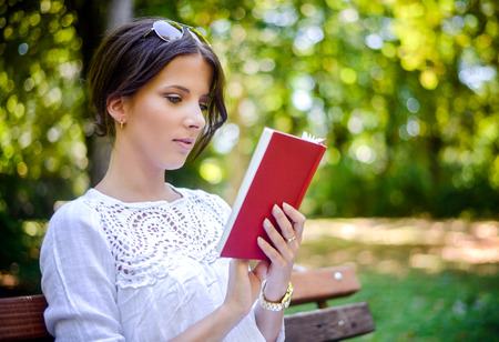 Serene young woman wearing a white lace blouse and reading an interesting book with red cover while sitting on a bench in the park in a warm day of spring or summer