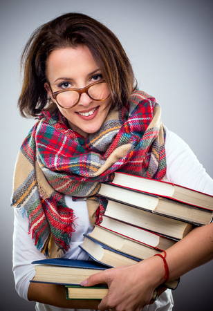 Happy stylish woman in a colorful winter scarf and eyeglasses holding a pile of hardcover books under her arm as she smiles at the camera Stock Photo