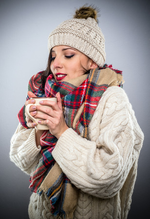 warmly: Attractive woman warmly dressed in a trendy winter outfit with colorful scarf enjoying a hot cup of coffee as she cradles it in her hands savoring the aroma