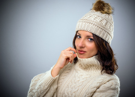 Pretty brunette woman in warm winter fashion wearing a woollen cap and matching cable-knit polo neck sweater turning to look at the camera with a smile, head and shoulders on grey with copy space Stock Photo