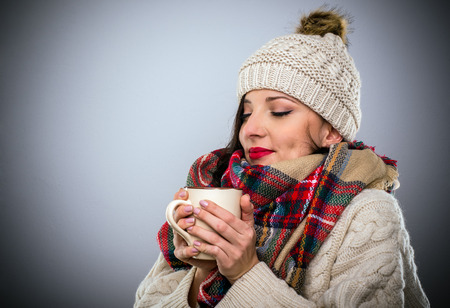 Blissful woman cuddling down into her warm winter scarf enjoying a mug of hot coffee cradled in her hands with a smile pleasure, over grey with copy space