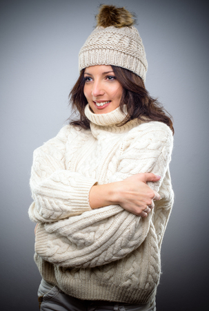 Smiling young woman in a fashionable knitted winter outfit with a cream coloured jersey and hat standing with folded arms looking off to the side Stock Photo