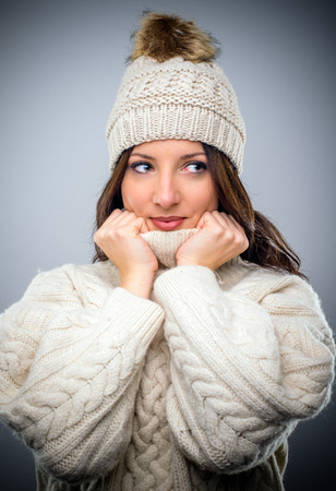 Pretty young woman in winter fashion in a matching knitted jersey and scarf snuggling into the warm polo neck collar with a smile, looking off to the side on a grey background