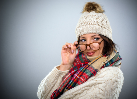 Glamorous woman wearing a stylish scarf with a woollen winter jersey and cap glancing over her glasses with a smile over a grey background with copy space