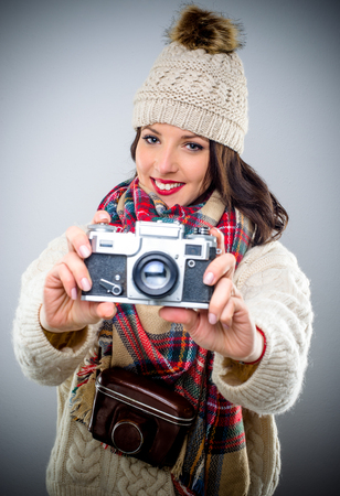 Studio shot of woman with photo camera