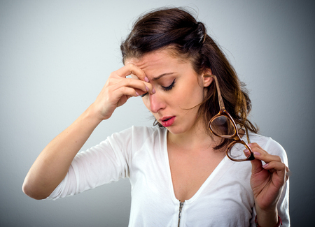 Attractive young woman with a headache holding her glasses in one hand as she pinches the bridge of her nose with a pained expression, head and shoulders on grey Stock Photo