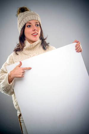 Pretty young woman wearing a turtleneck sweater and knitted woollen cap pointing to a blank white sign with copy space that she is holding in front of her chest Stock Photo