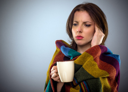 Young woman feeling unwell rubbing her temple with her hand with a troubled expression as she stands wrapped in a blanket with a cup of coffee, with copy space