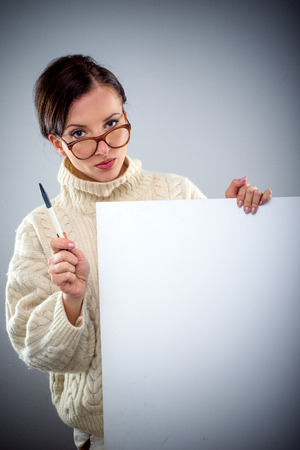 Scholarly attractive serious young woman holding a blank white sign as she peers over her glasses at the camera with a pen in her hand Stock Photo