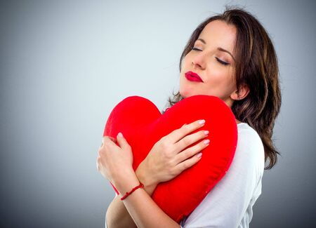 sentimental: Romantic sentimental attractive young woman with a red heart clasped in her arms and her eyes closed in bliss, conceptual of Valentines Day, with copy space