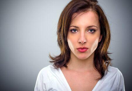 niñas bonitas: Grave joven atractiva que pone mala cara sus labios con lápiz labial rojo colorido como ella t mira la cámara, cabeza y los hombros sobre fondo gris con espacio de copia