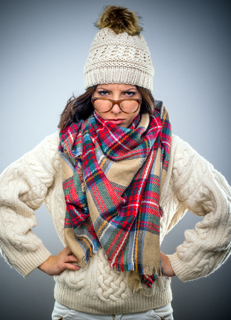 glaring: Grumpy attractive young woman in winter fashion wearing a colorful scarf and glasses perched on her nose, glaring at the camera with her hands on her hips