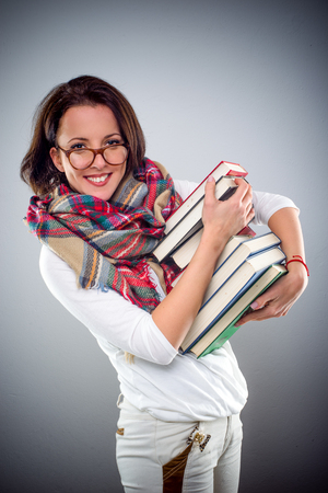 Trendy attractive woman wearing a scarf and glasses carrying a large pile of books under arm smiling at the camera, on grey with vignette