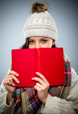 coy: Coy young woman in a woolly winter cap reading a red hardcover book holding it to her face as she peers over the top at the camera Stock Photo