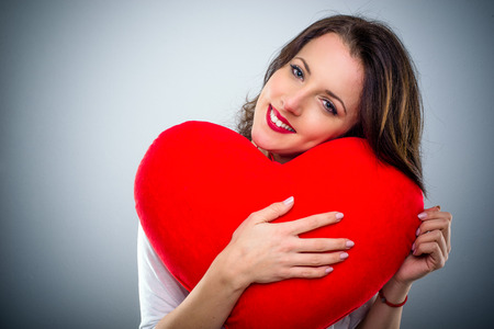 Sentimental young woman in love hugging a large red heart with a tender smile in a Valentines Day concept